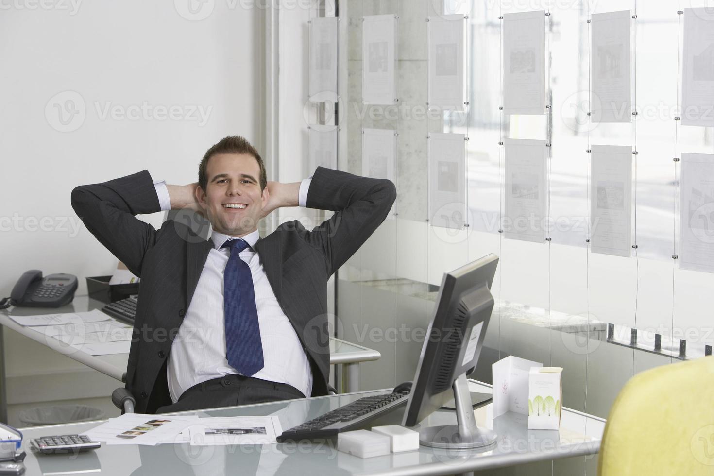 ontspannen zakenman zit aan balie in kantoor foto