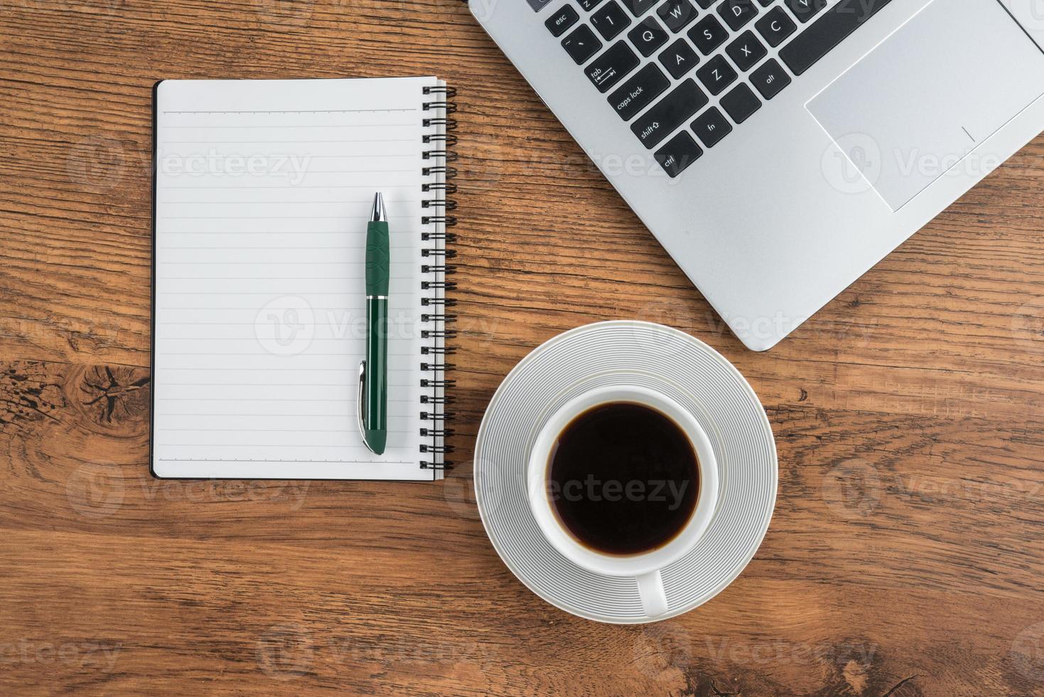 laptop, notebook en koffiekopje op Bureau foto
