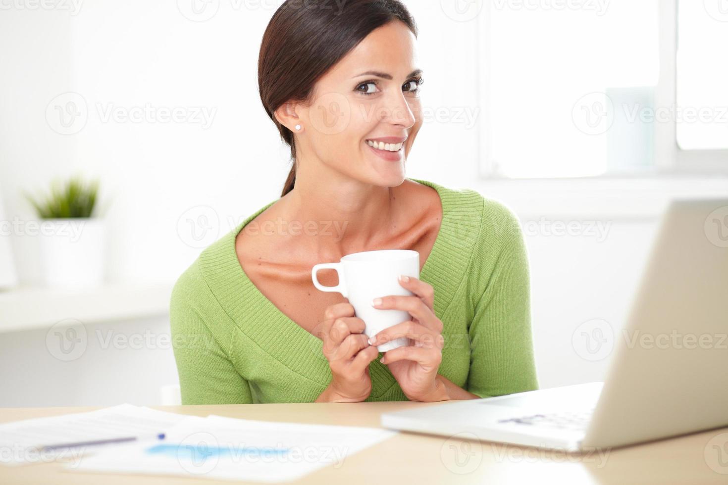 Spaanse jonge vrouw zitten en werken op het bureau foto