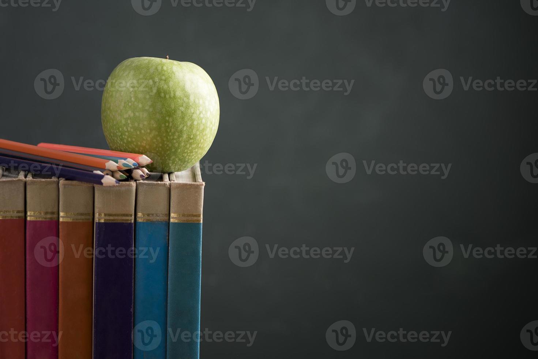 boeken op het bureau van de klas met een schoolbord foto