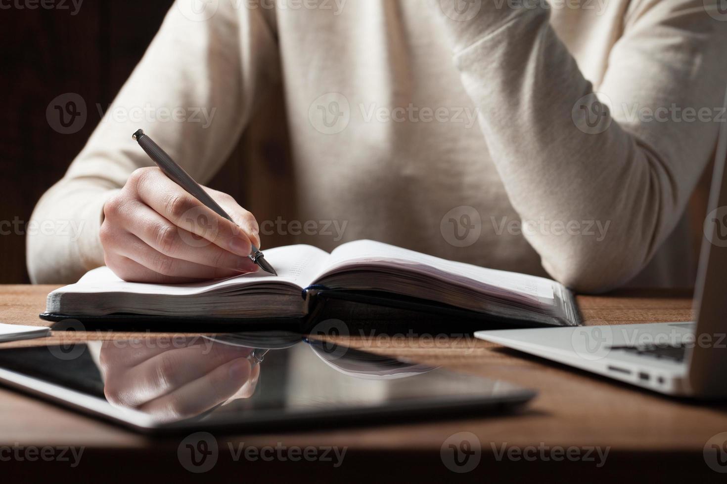 vrouwenhanden die laptop met behulp van bij bureau foto