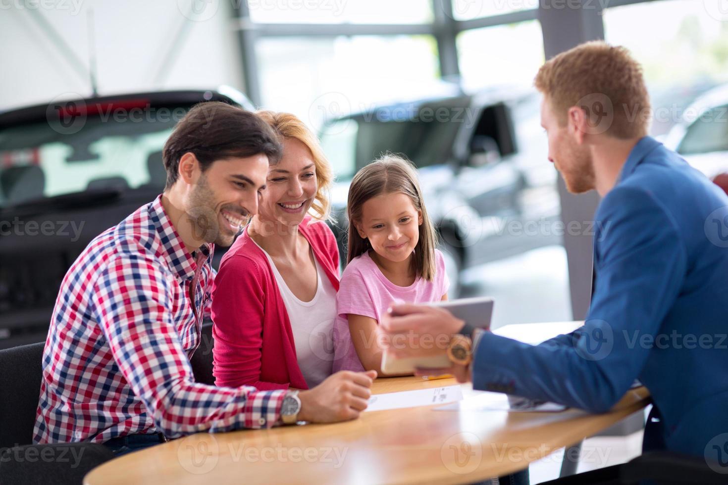 jong gezin in autodealer foto