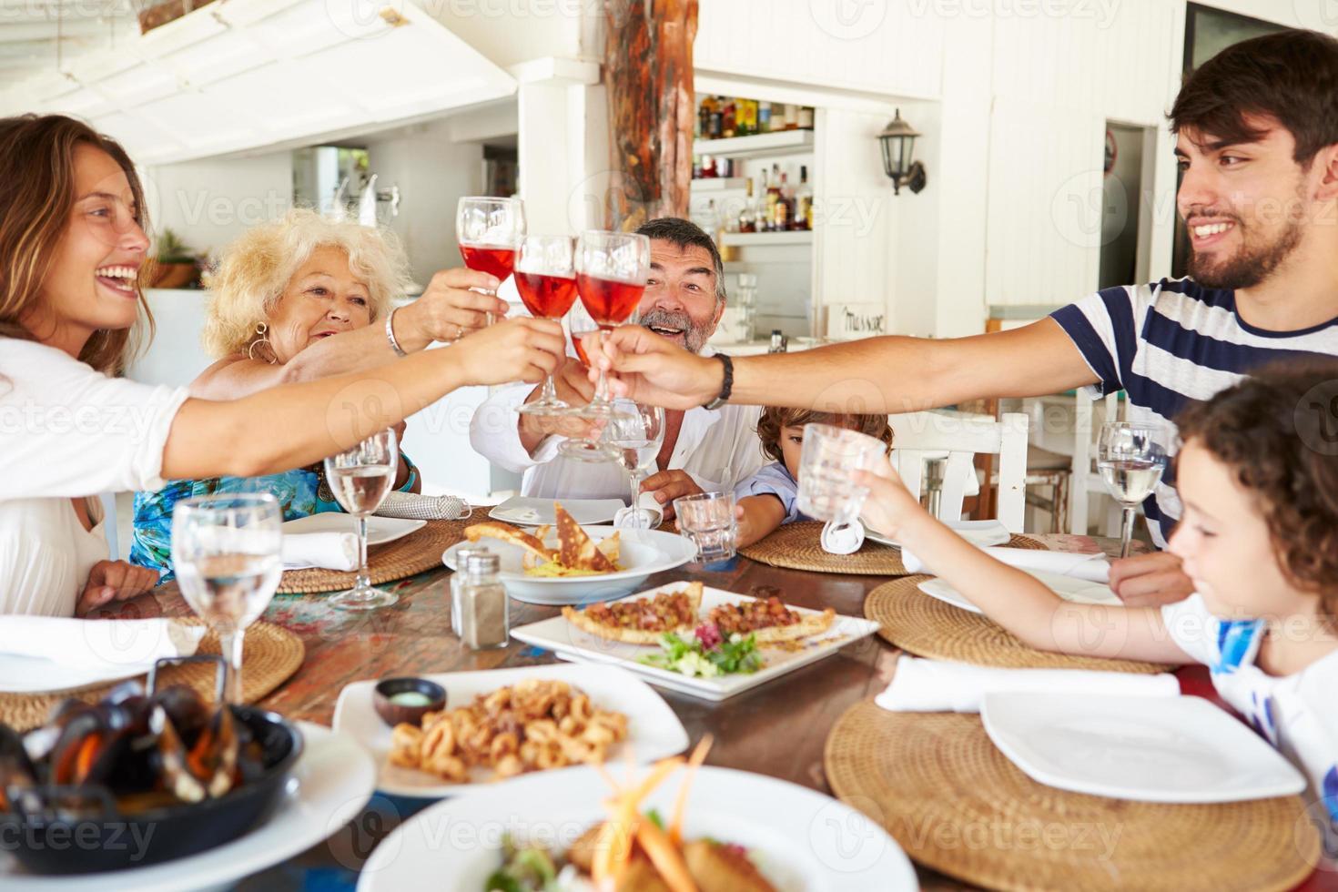 familie van meerdere generaties die van maaltijd in restaurant genieten foto