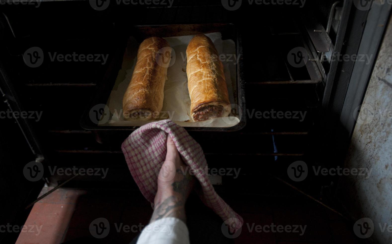 twee worstenbroodjes die uit de oven komen foto