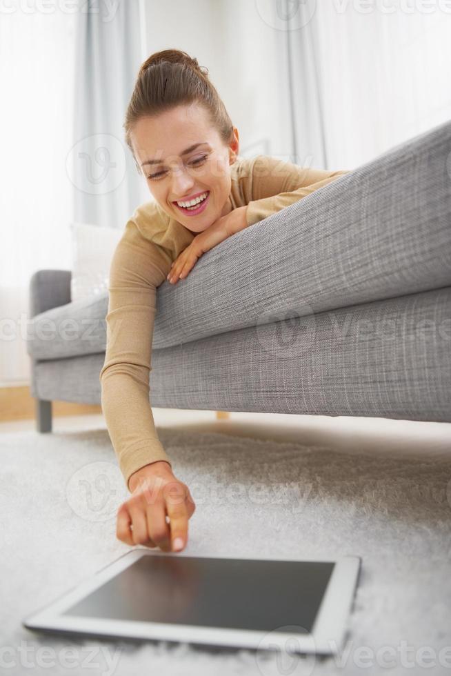 gelukkige jonge vrouw die tabletpc gebruikt terwijl het leggen van bank foto