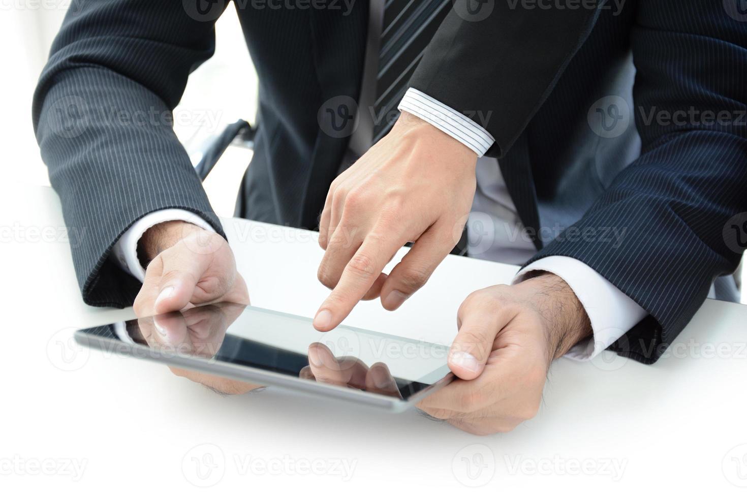 twee zakenlieden met behulp van tablet-computer met één hand scherm aan te raken foto