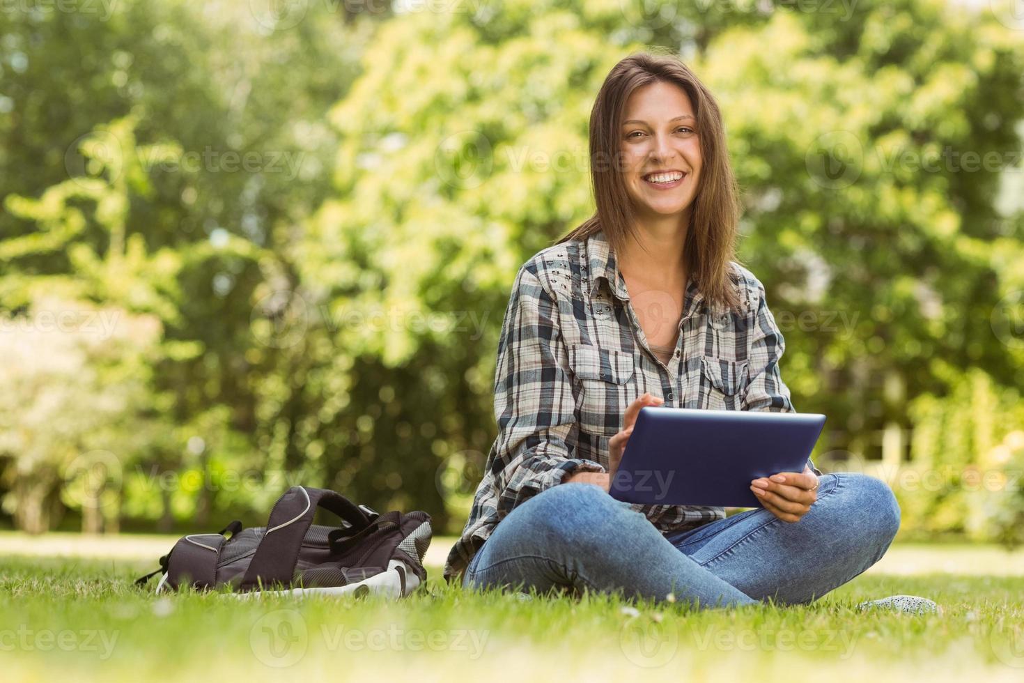 lachende student zitten en het gebruik van tablet-pc foto