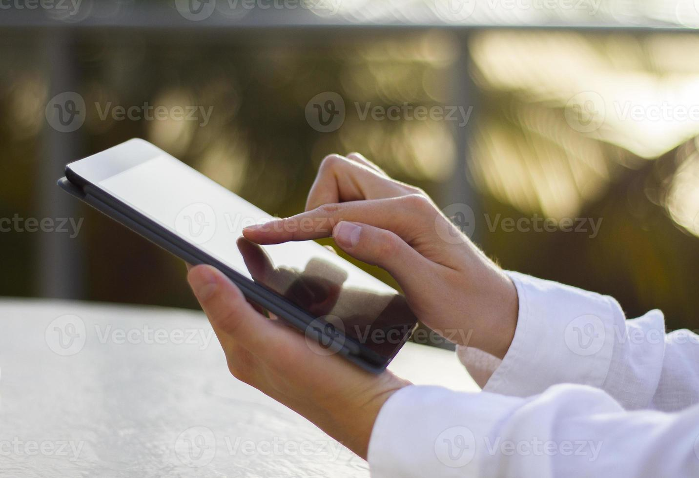 man klikt op een digitale tablet bij zonsopgang foto