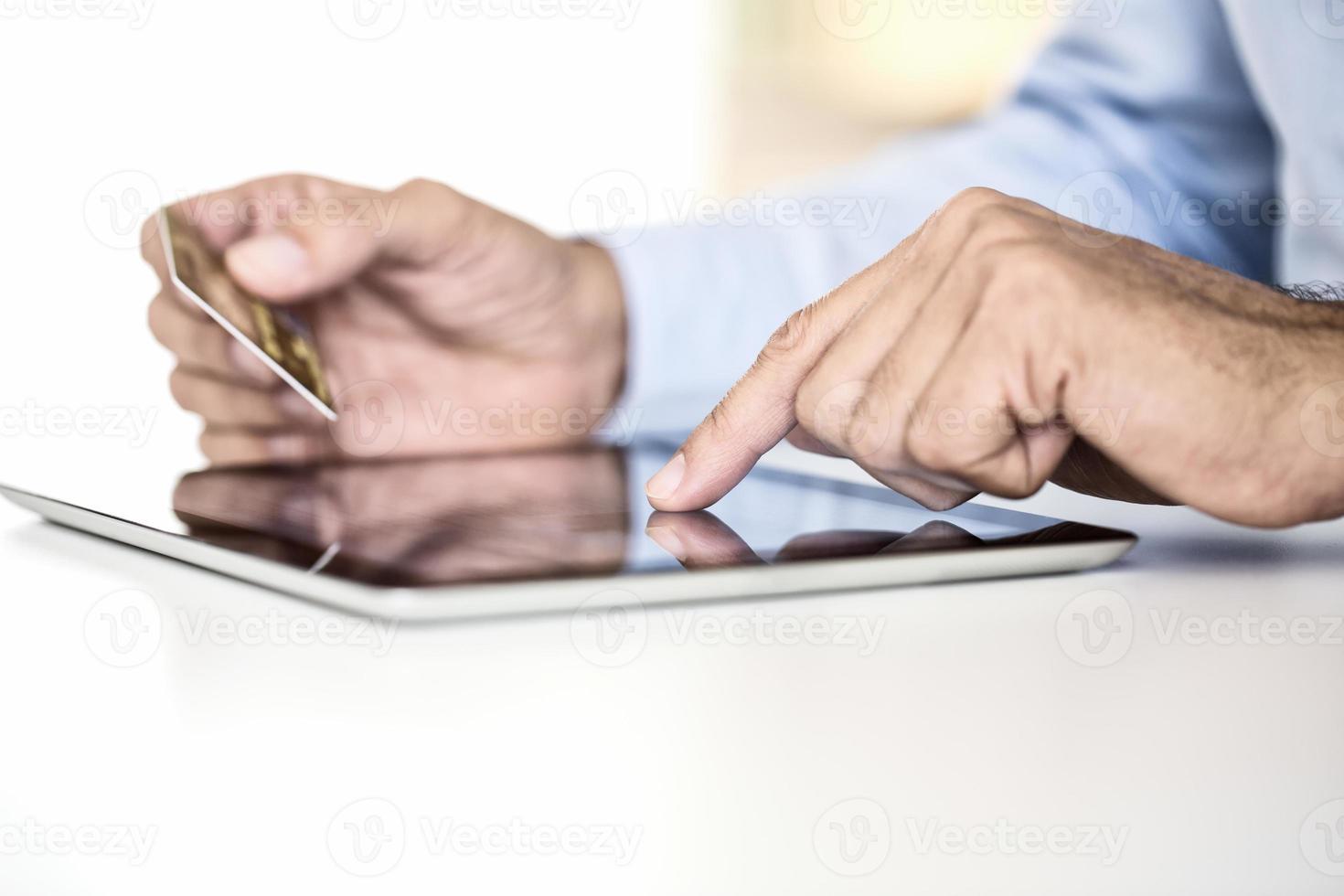man met behulp van tablet pc en creditcard indoor, online winkelen foto