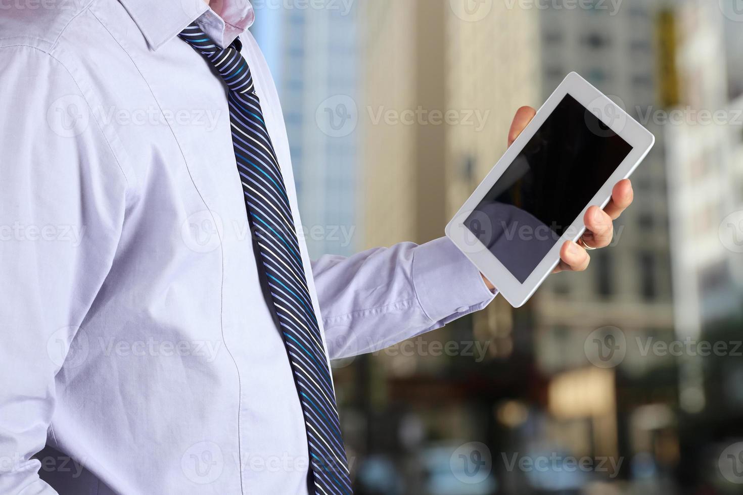 zakenman die en de digitale tablet in het bureau houden gebruiken foto