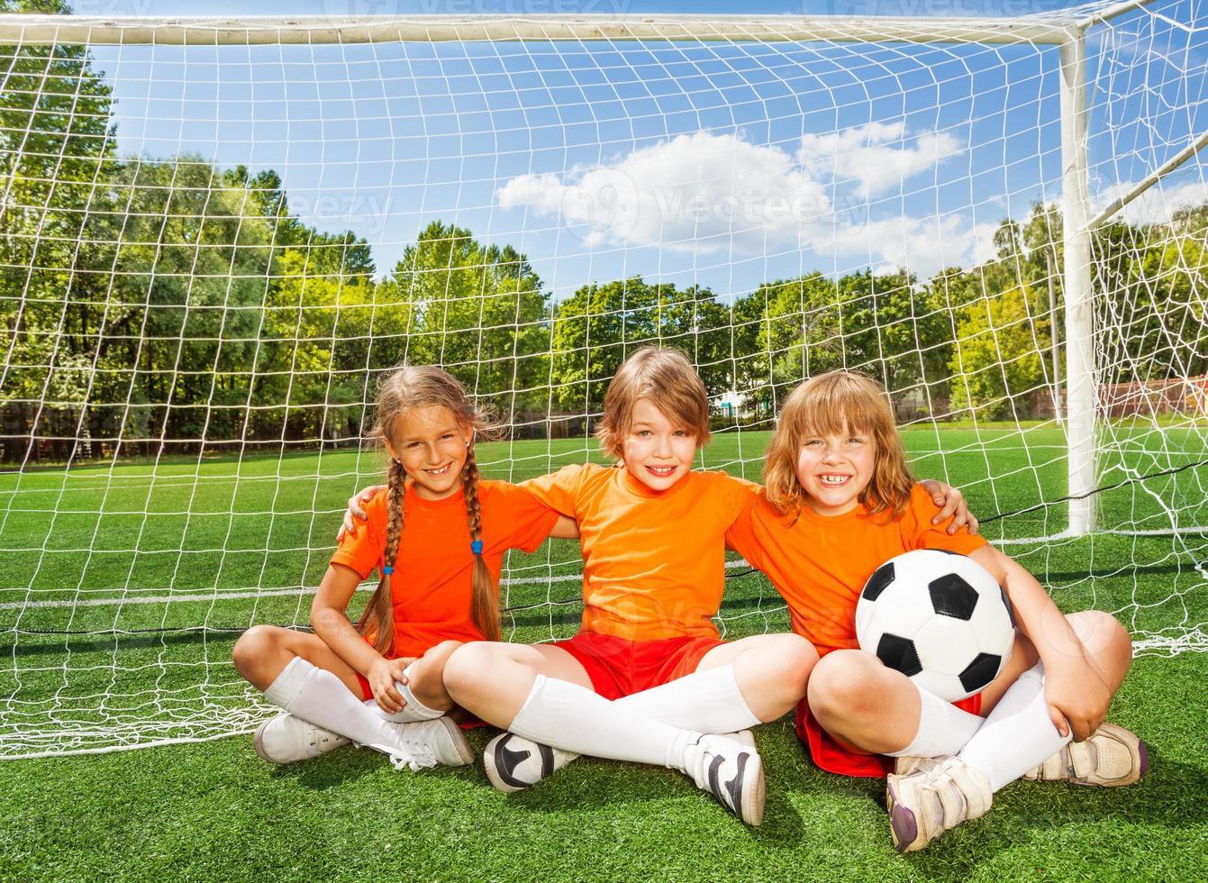 lachende kinderen zitten op gras met voetbal foto