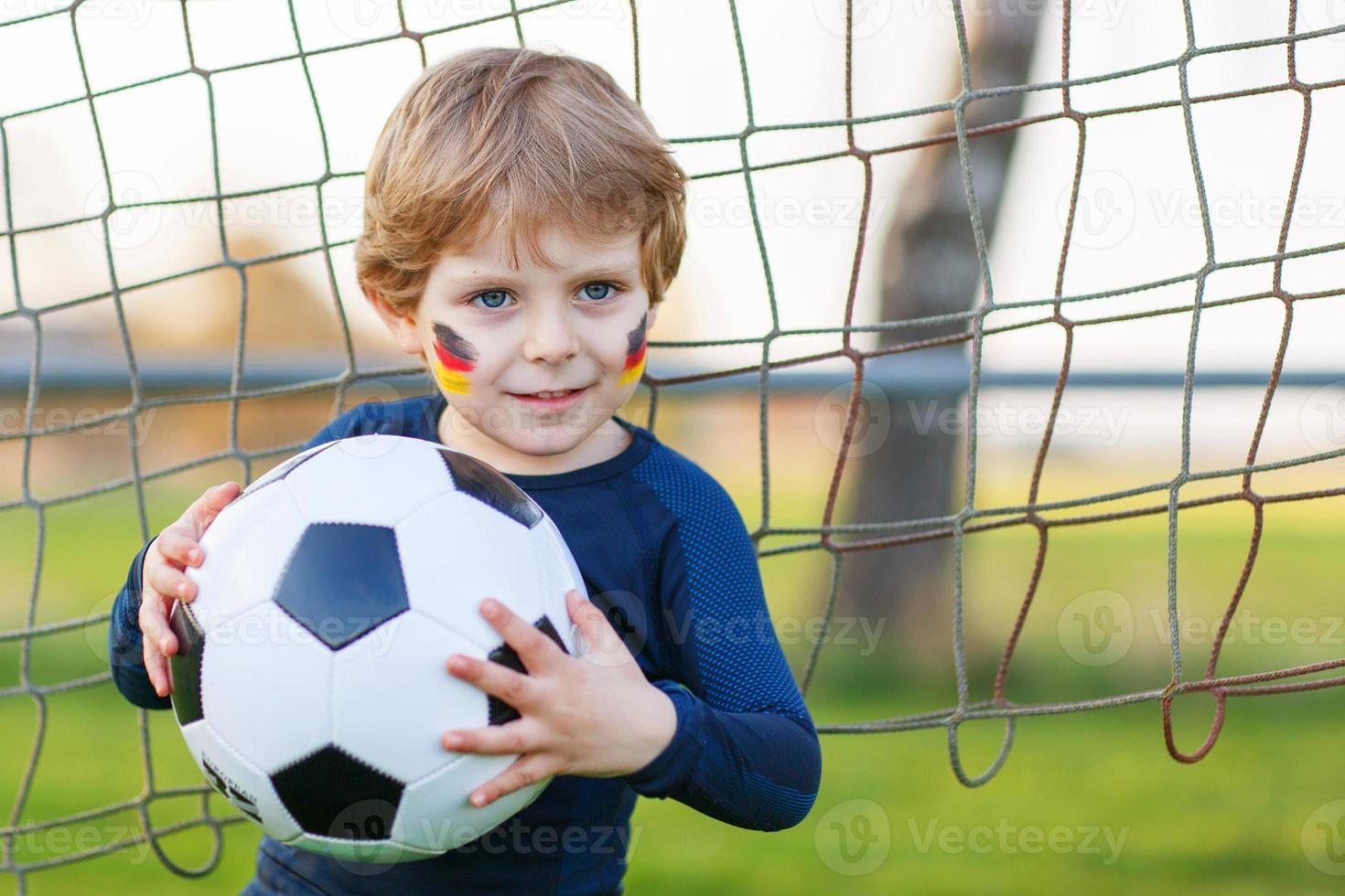 kleine fan jongen bij het openbaar bekijken van voetbal of voetbal foto