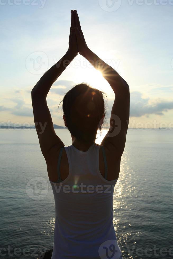 gezonde yoga vrouw meditatie bij zonsopgang aan zee foto