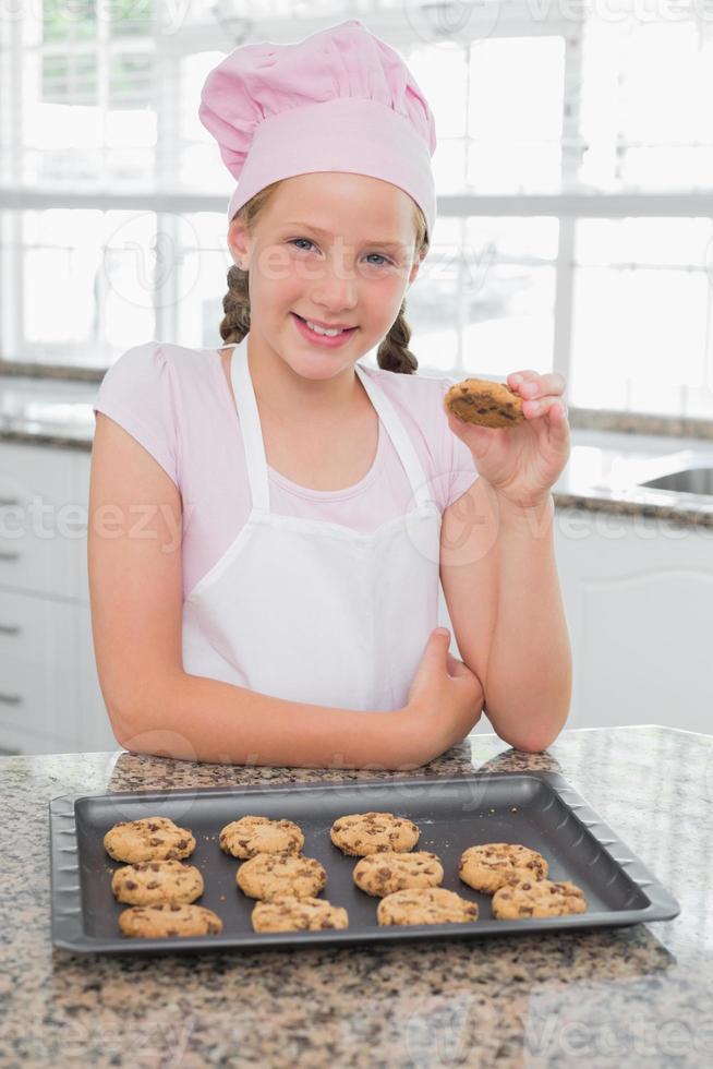 glimlachend jong meisje dat van koekjes in keuken geniet foto