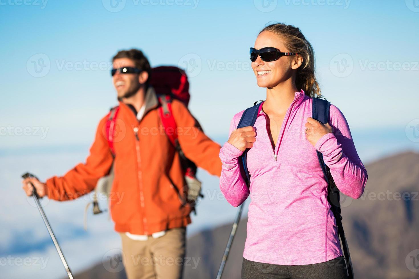 wandelaars genieten van het uitzicht vanaf de bergtop foto