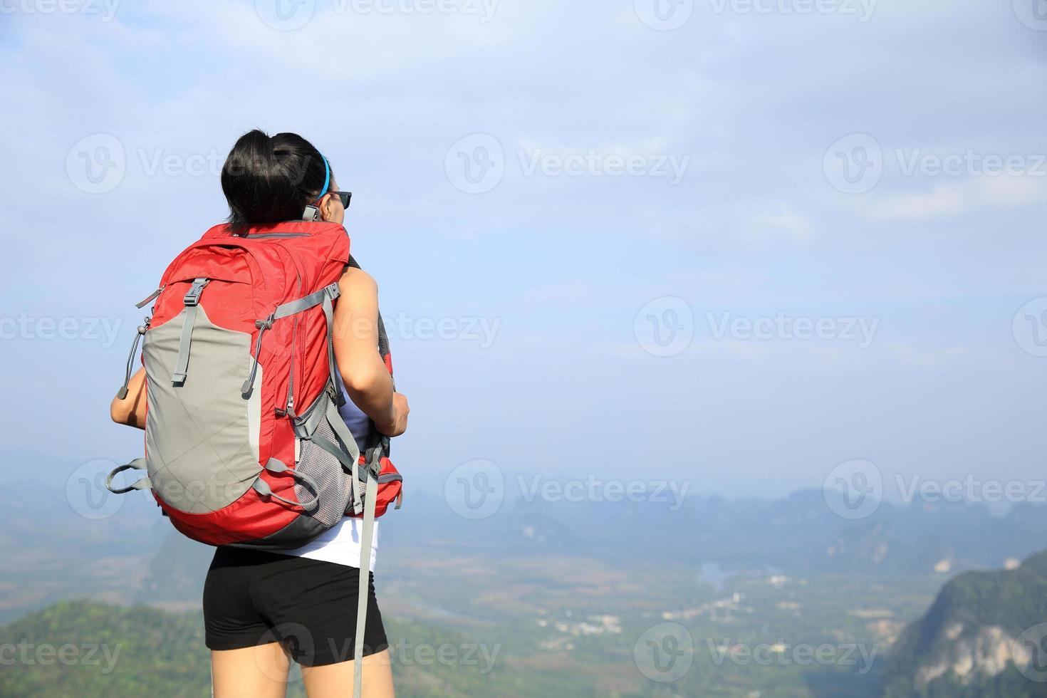 vrouw wandelaar geniet van het uitzicht bij zonsondergang bergtop foto