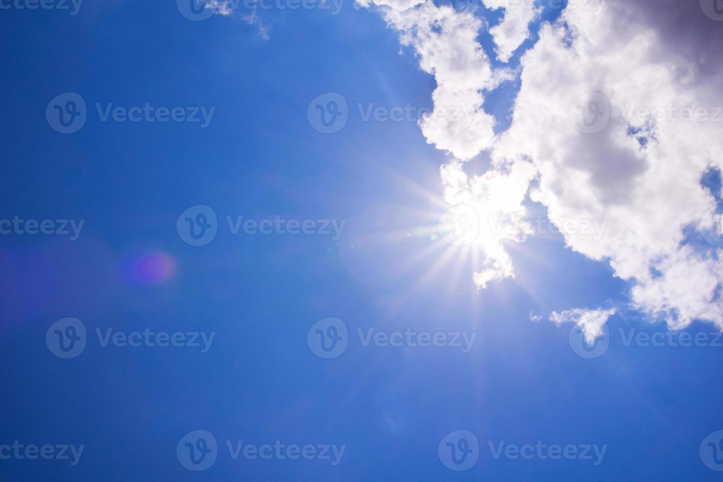 realistische stralende zon met lensflare. blauwe lucht met wolken foto