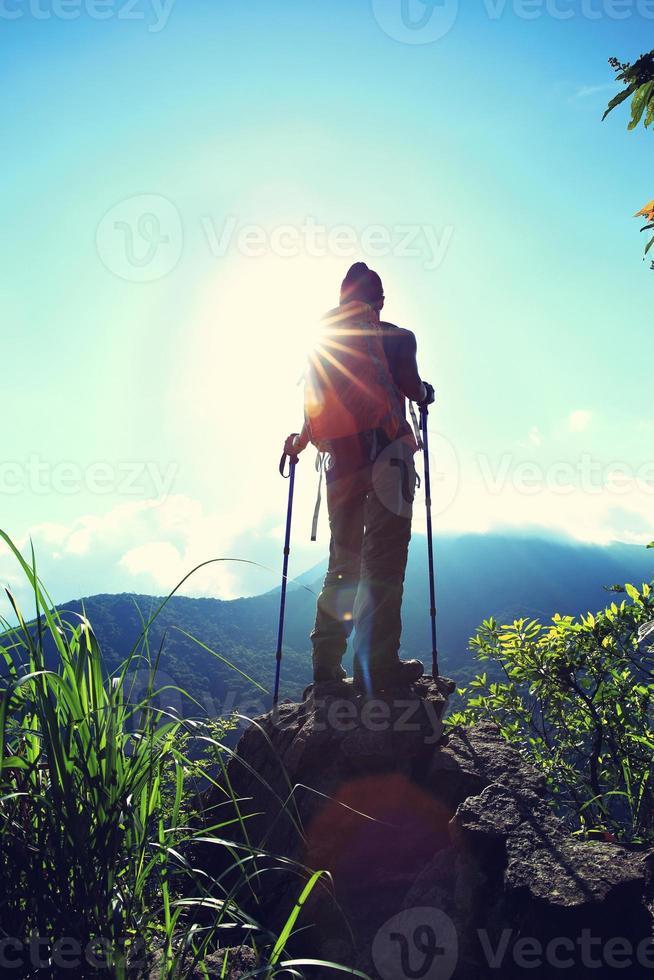 juichende vrouw wandelaar geniet van het uitzicht op de bergtop klif foto