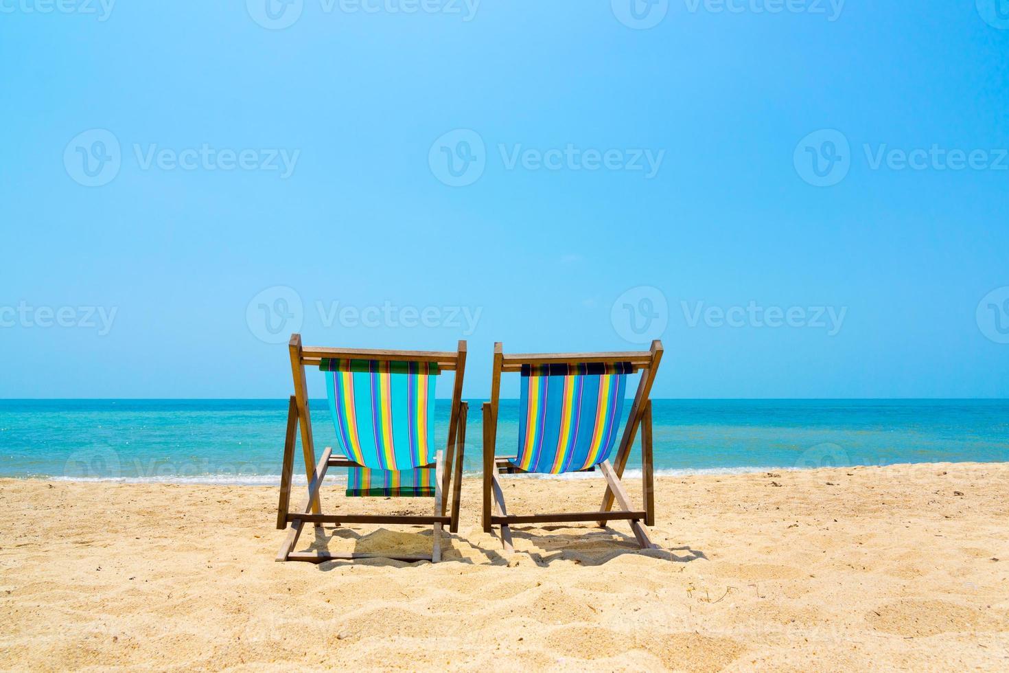 twee ligstoelen op het strand foto