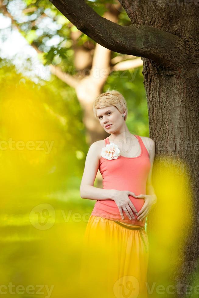 jonge gelukkig zwangere vrouw ontspannen in de natuur foto