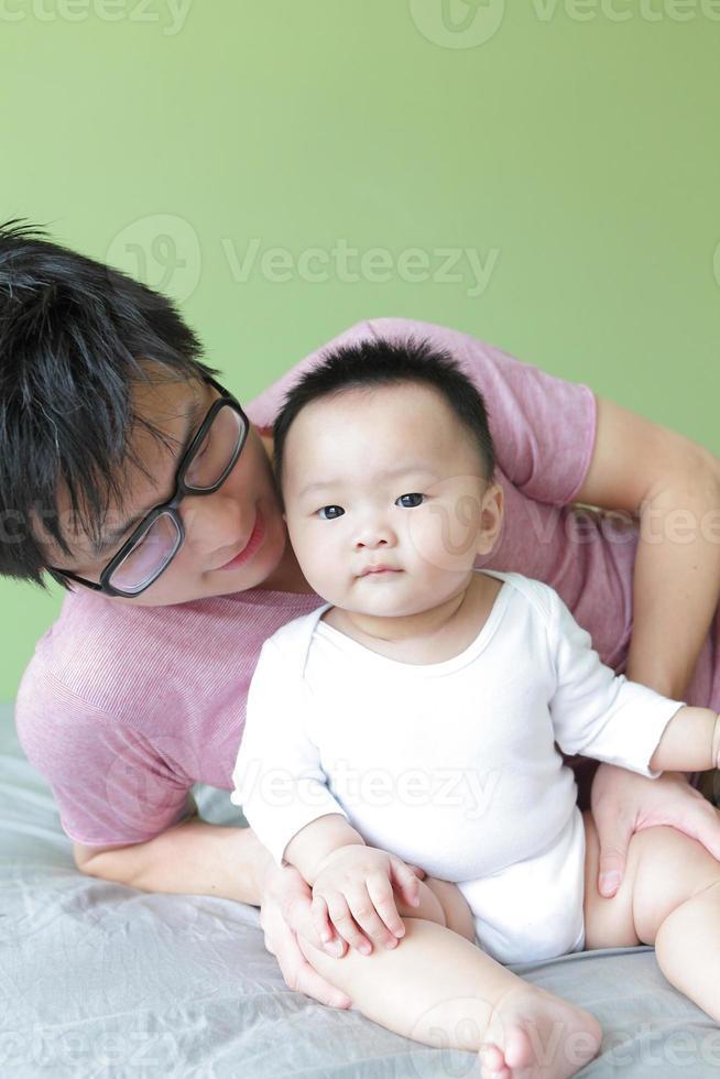 jonge vader gelukkig spelen met zijn baby foto