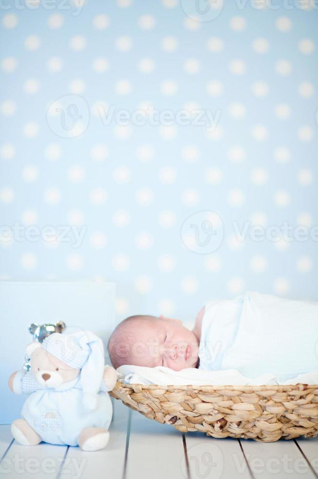 foto van een pasgeboren baby opgerold slapen in de mand