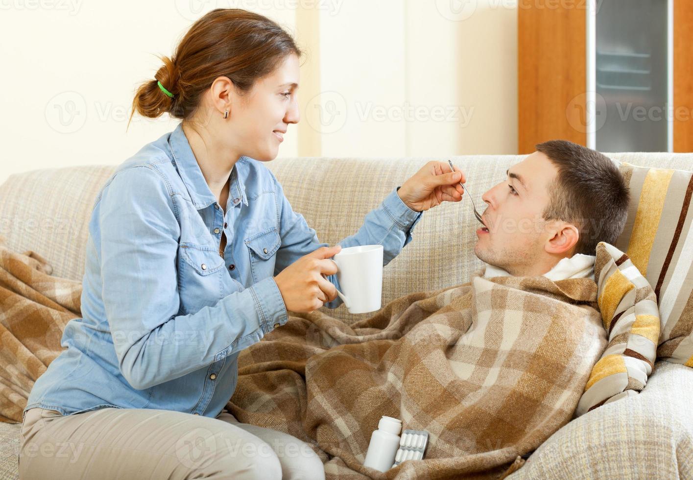 vrouwen die tabletten geven aan haar man foto