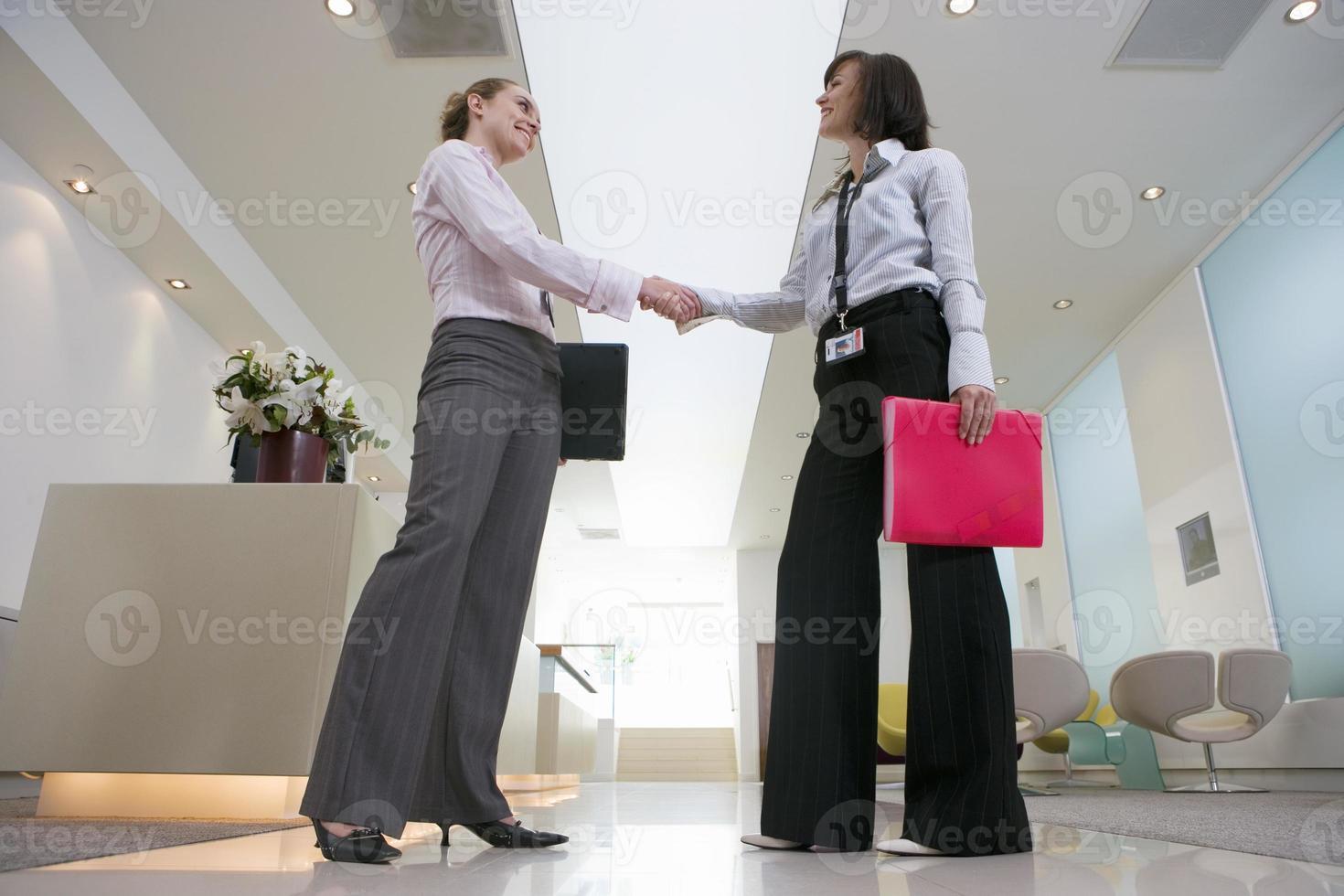twee ondernemers schudden handen in de lobby, glimlachend, oppervlak foto