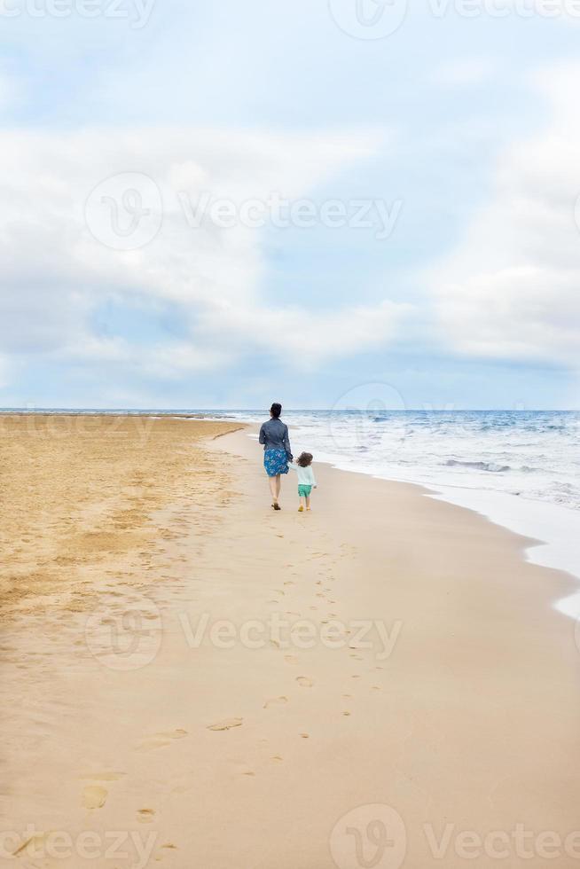 authentieke foto over moeder en dochter wandelen op het strand