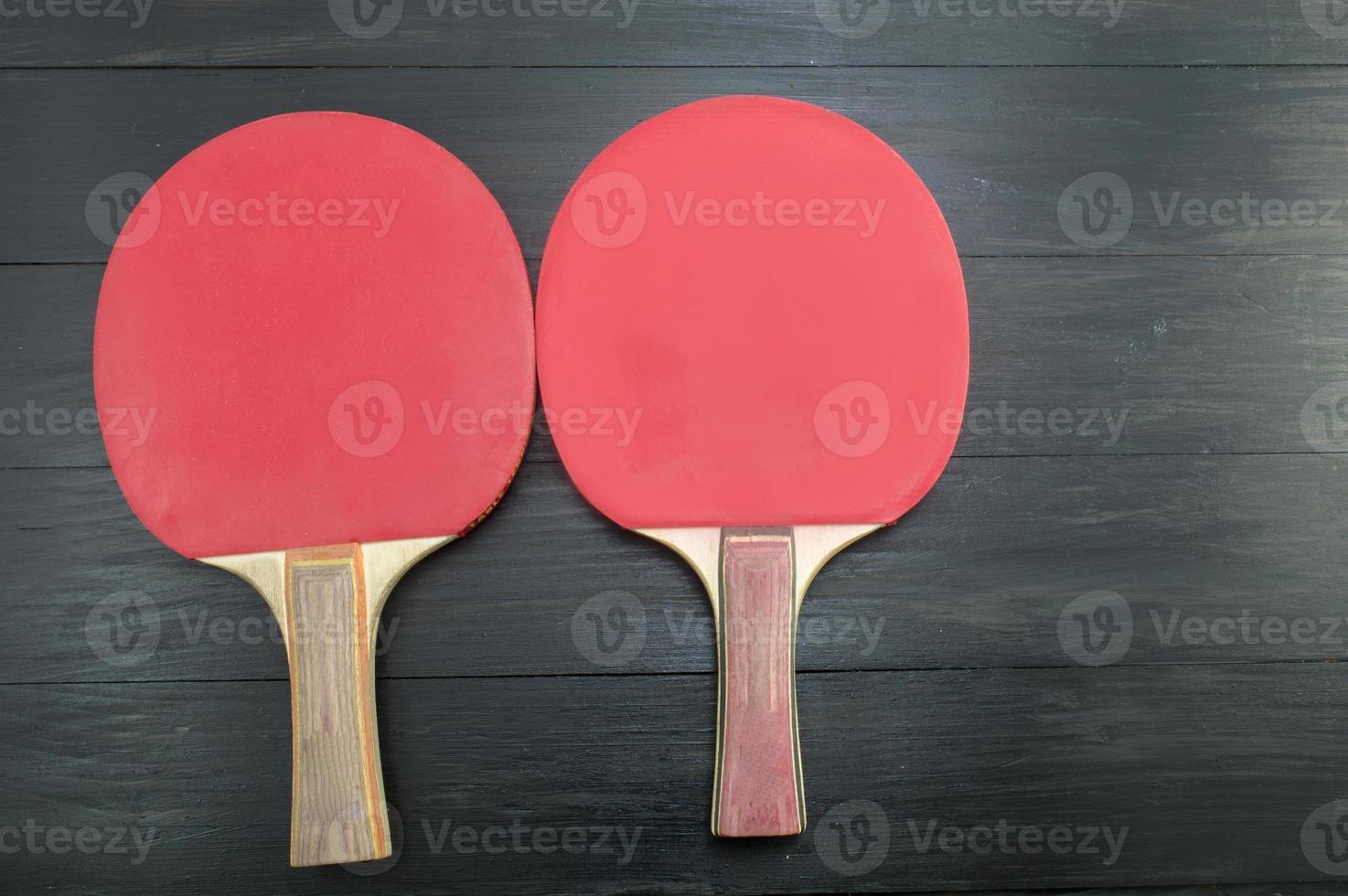 twee rode tafeltennis rackets op donkere achtergrond foto
