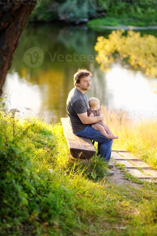 vader met zijn kleine baby zittend op houten bankje foto