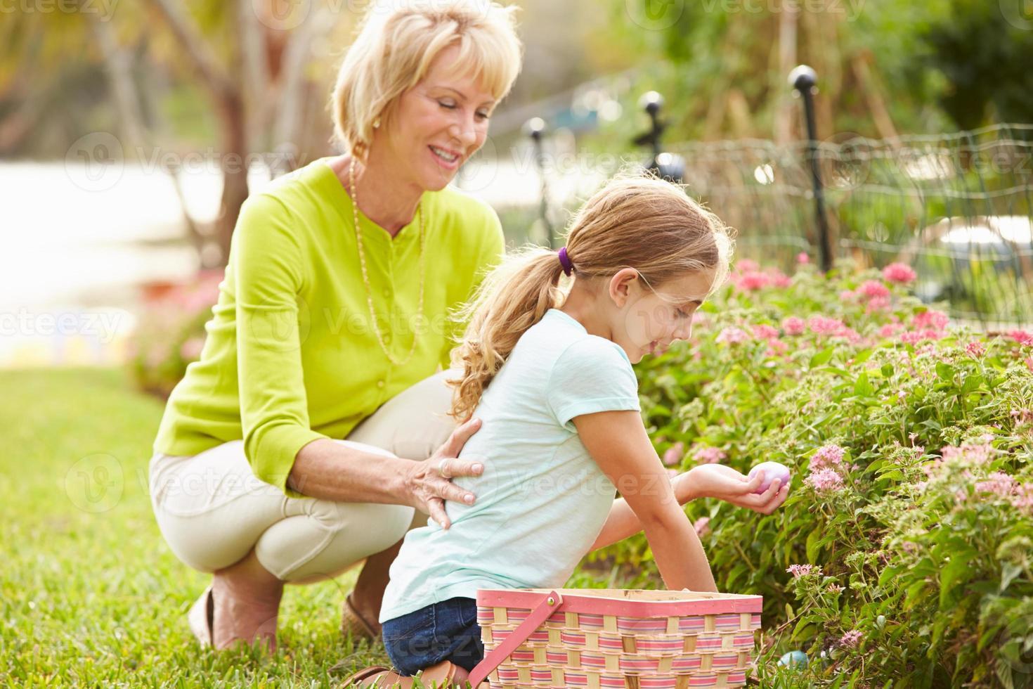 grootmoeder met kleindochter op paaseieren zoeken in de tuin foto
