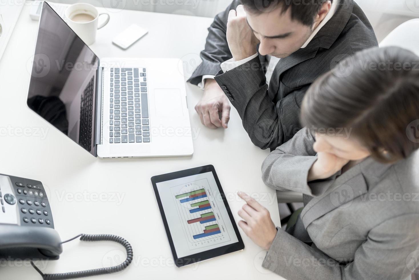 mannelijke en vrouwelijke zakenpartners die statistische jaarlijkse r analyseren foto