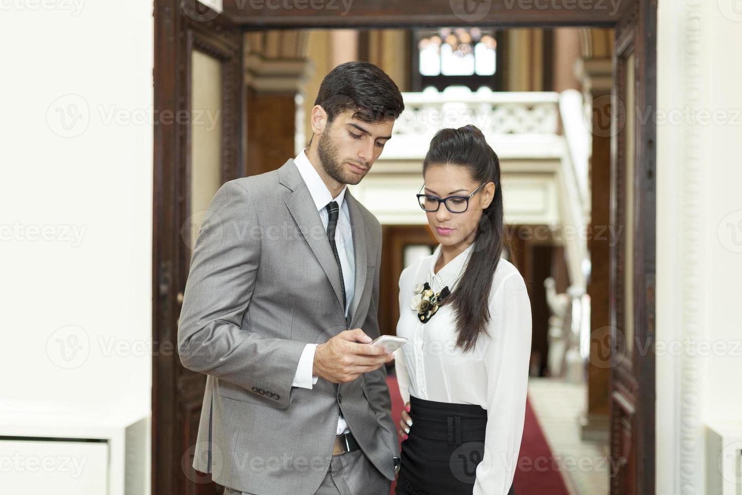 zakenman en zakenvrouw lezen van SMS-bericht foto