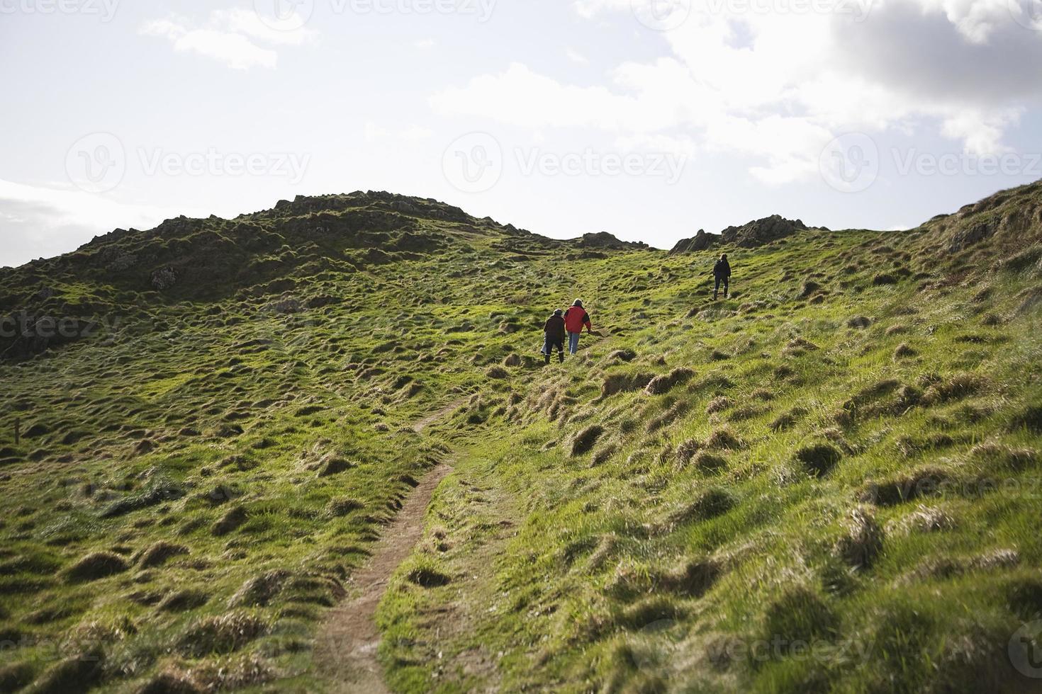 drie mensen klimmen heuvel op foto