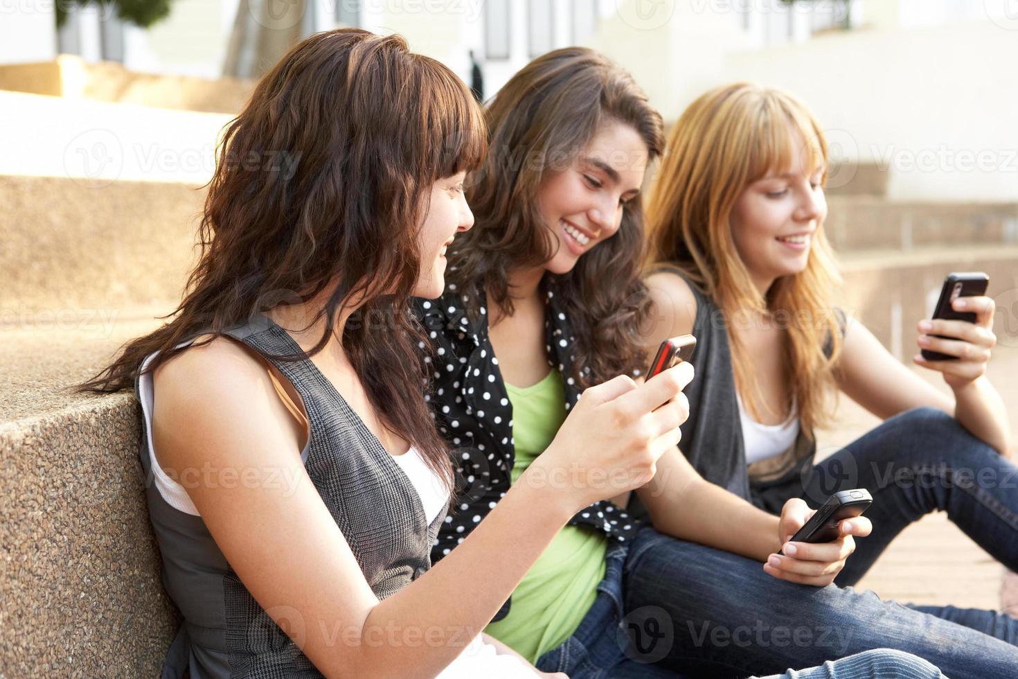 tienermeisjes zitten op de trappen van de campus en gebruiken telefoons foto