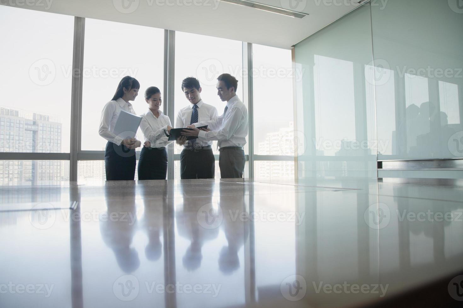 vier jonge mensen uit het bedrijfsleven staan bij de vergadertafel foto
