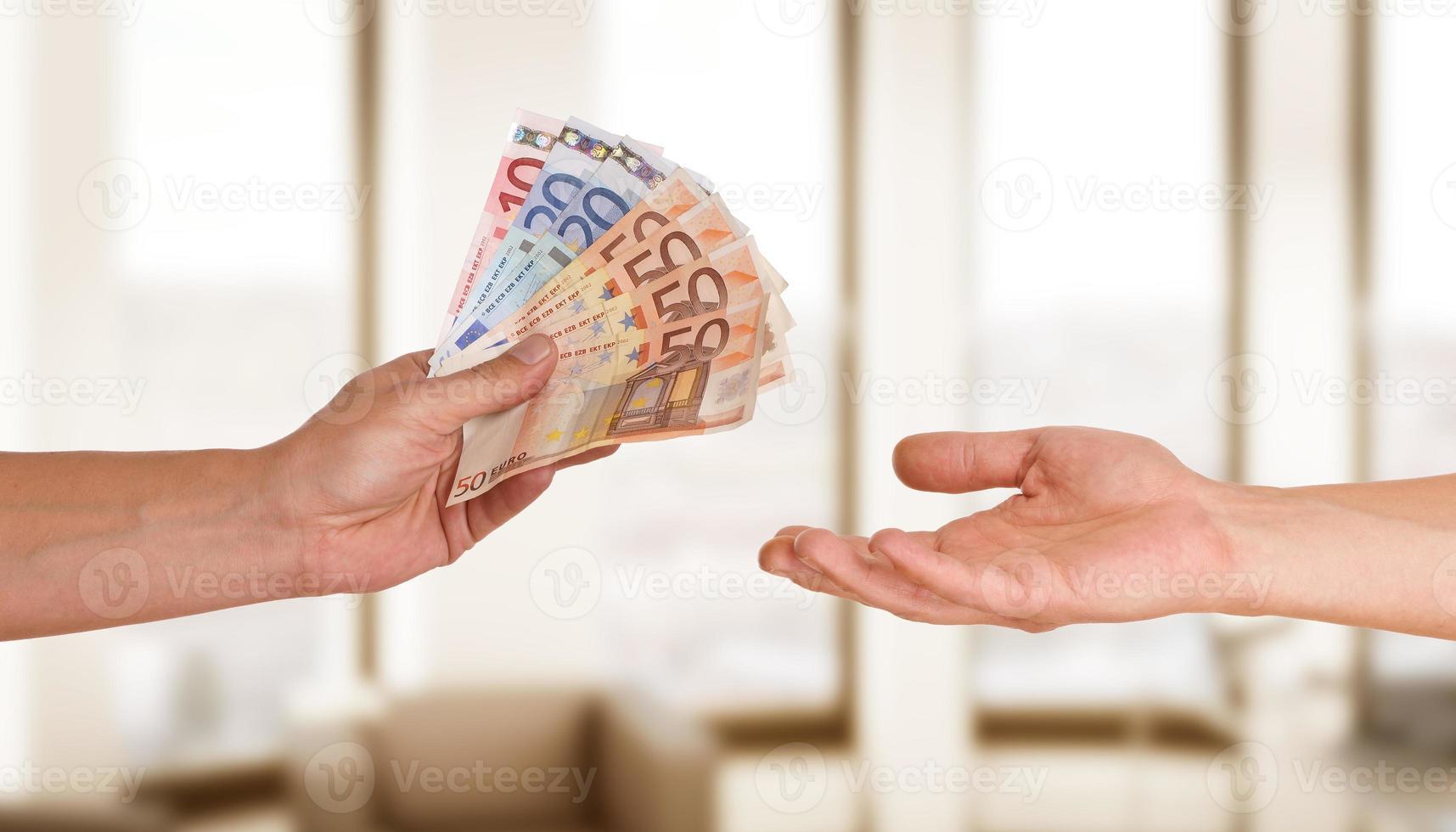 handen met geld met kleurrijke achtergrond foto