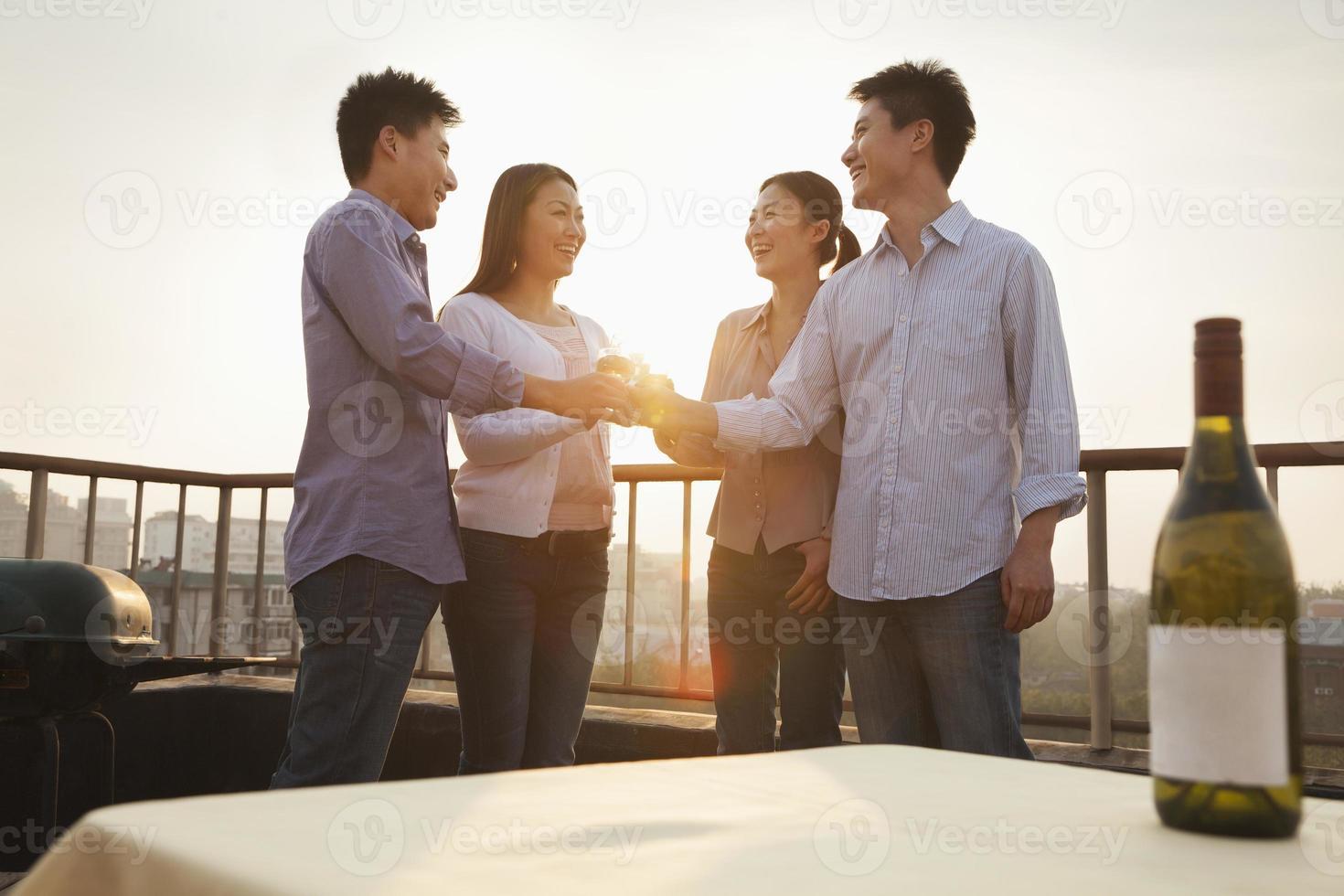 groep vrienden roosteren elkaar op het dak bij zonsondergang foto