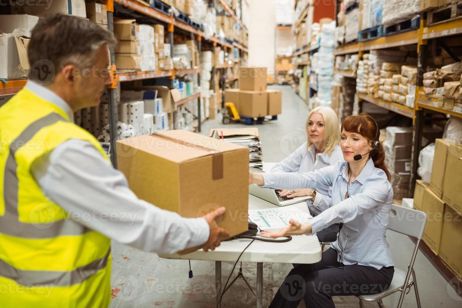 manager die geel vest draagt dat doos geeft aan zijn collega foto