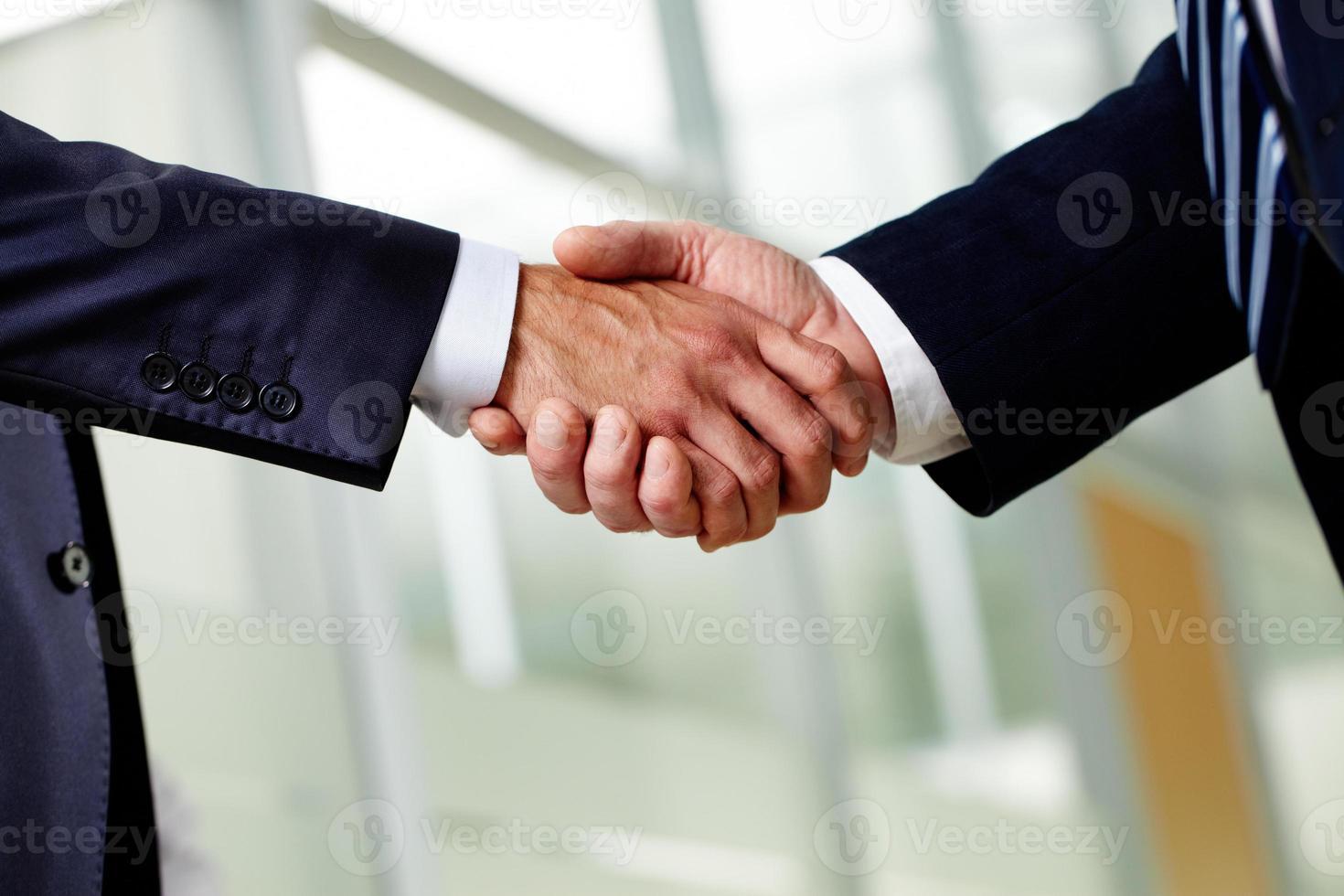 twee geschikte zakenlieden die handen stevig schudden foto