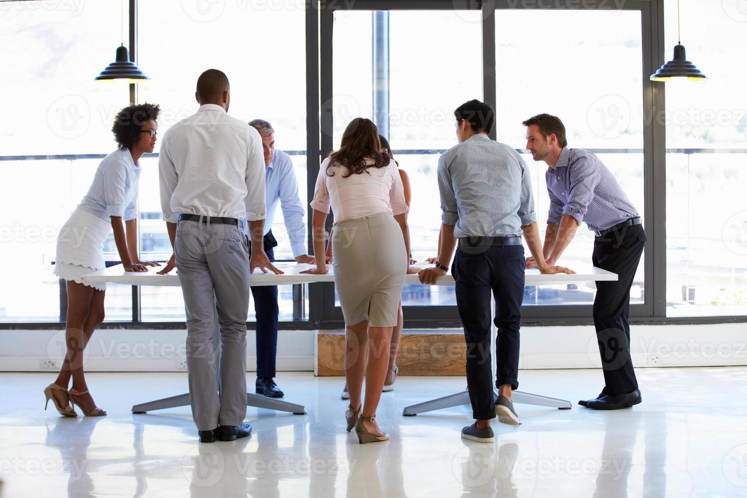 collega's staan rond een vergadertafel foto
