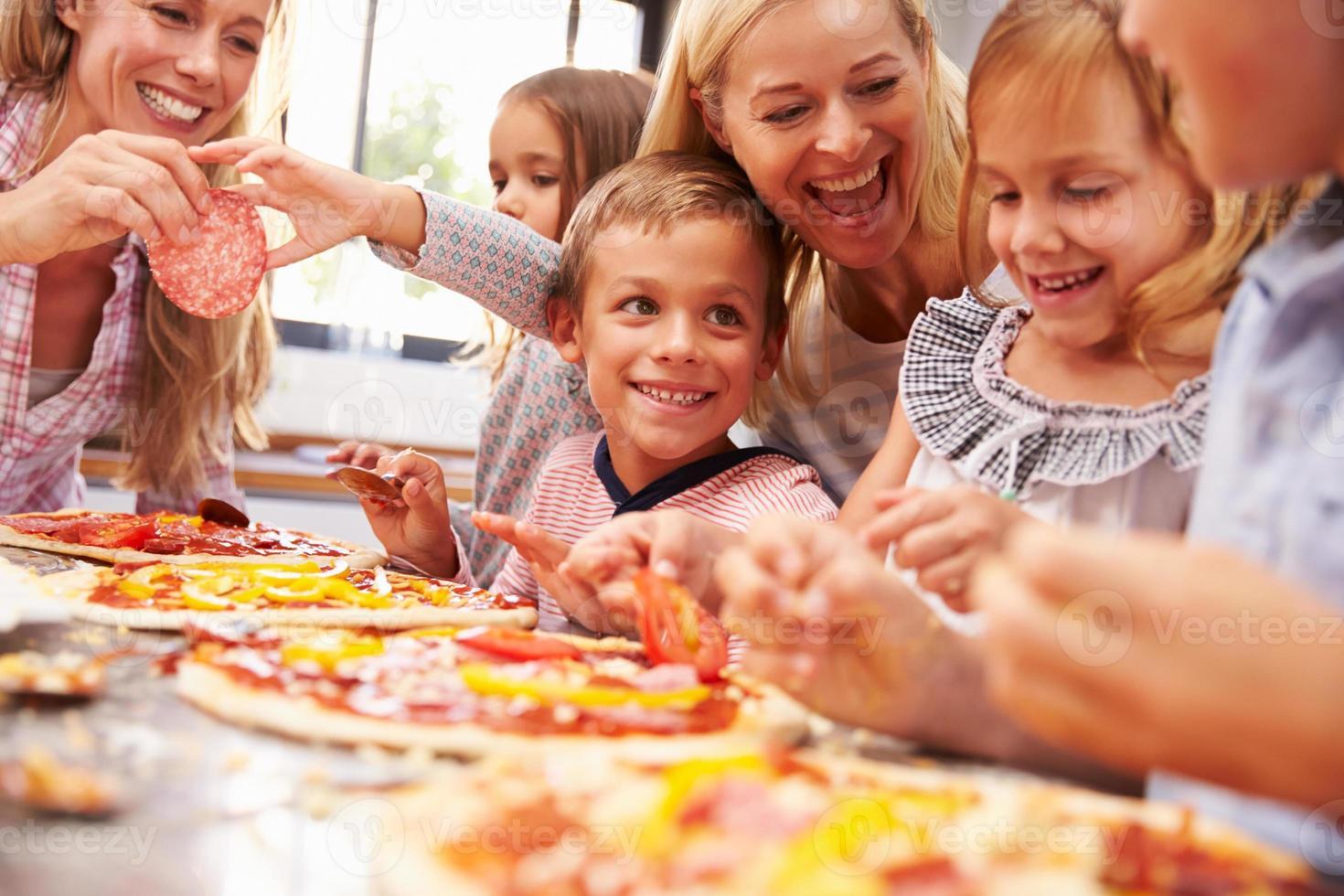 twee vrouwen die pizza maken met kinderen foto