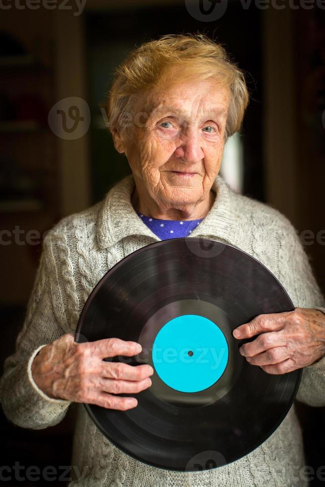 oude vrouw staat met het vinylplaat in zijn handen foto