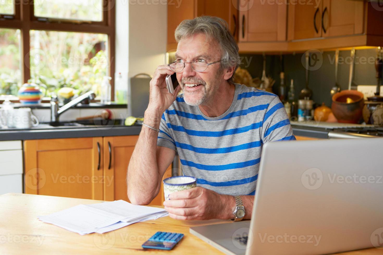 volwassen man met behulp van mobiele telefoon thuis financiën kijken foto