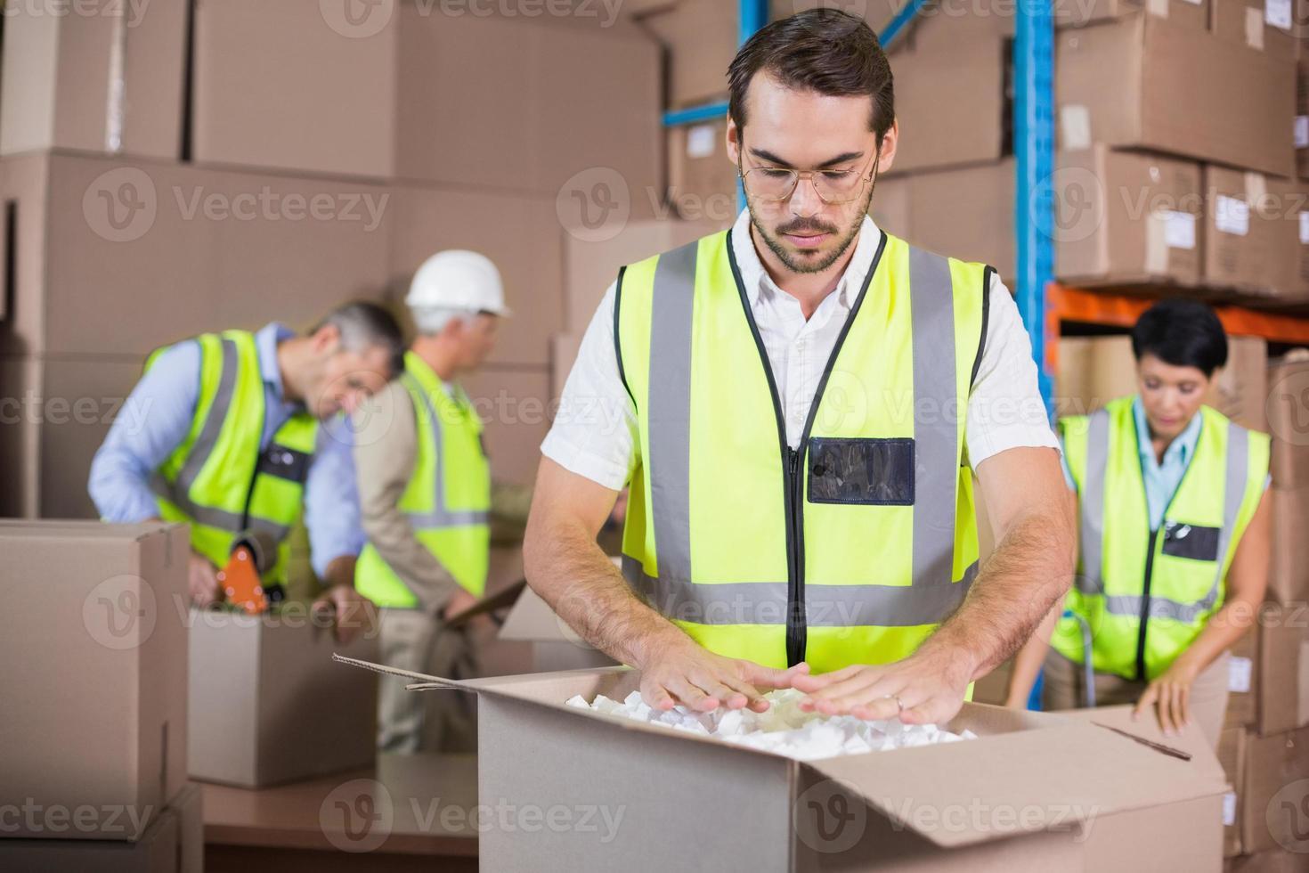 magazijnmedewerkers in gele hesjes die een verzending voorbereiden foto