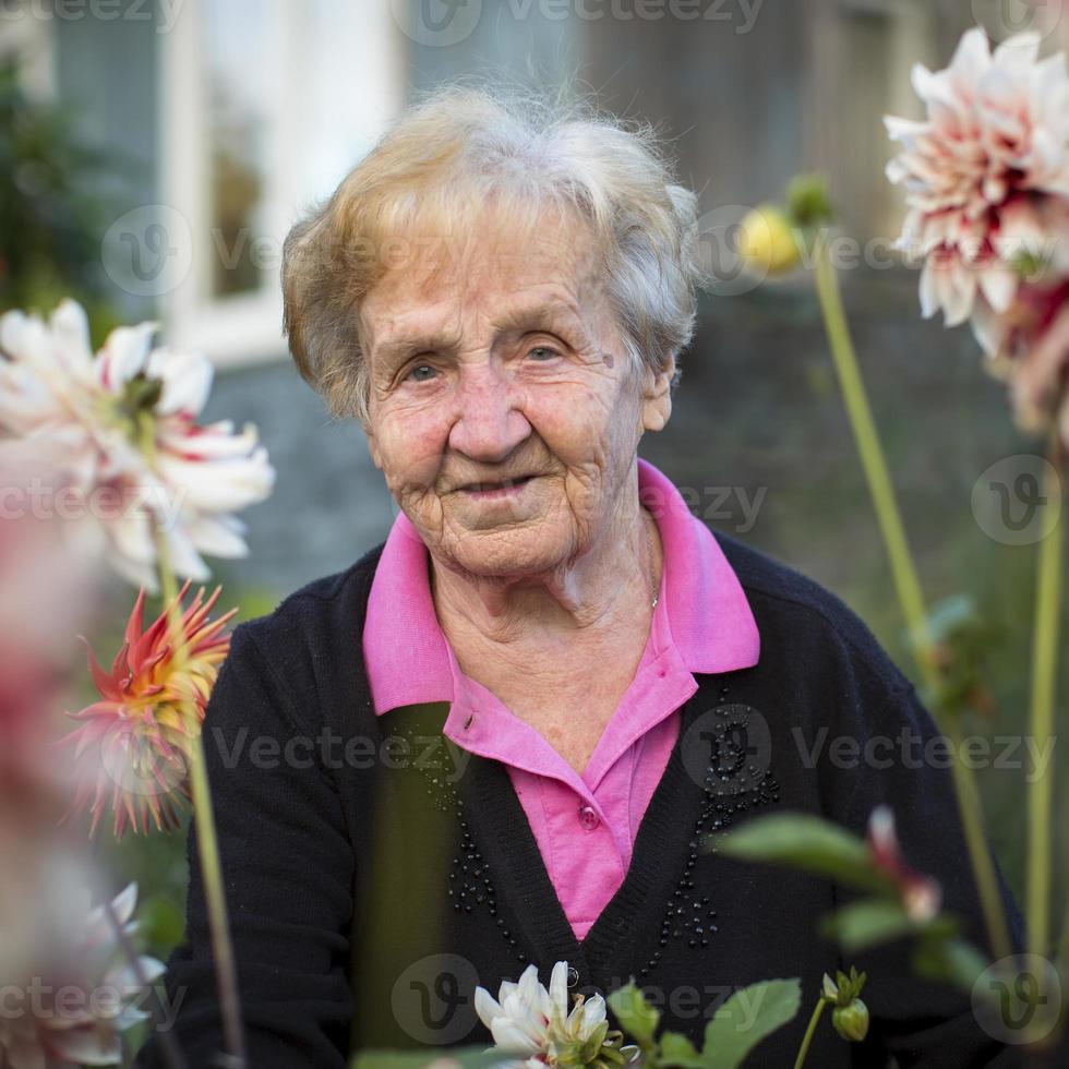 portret van een oudere vrouw in de tuin. foto