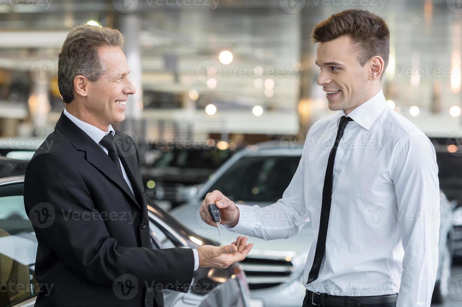 het geven van een sleutel van nieuwe auto. foto
