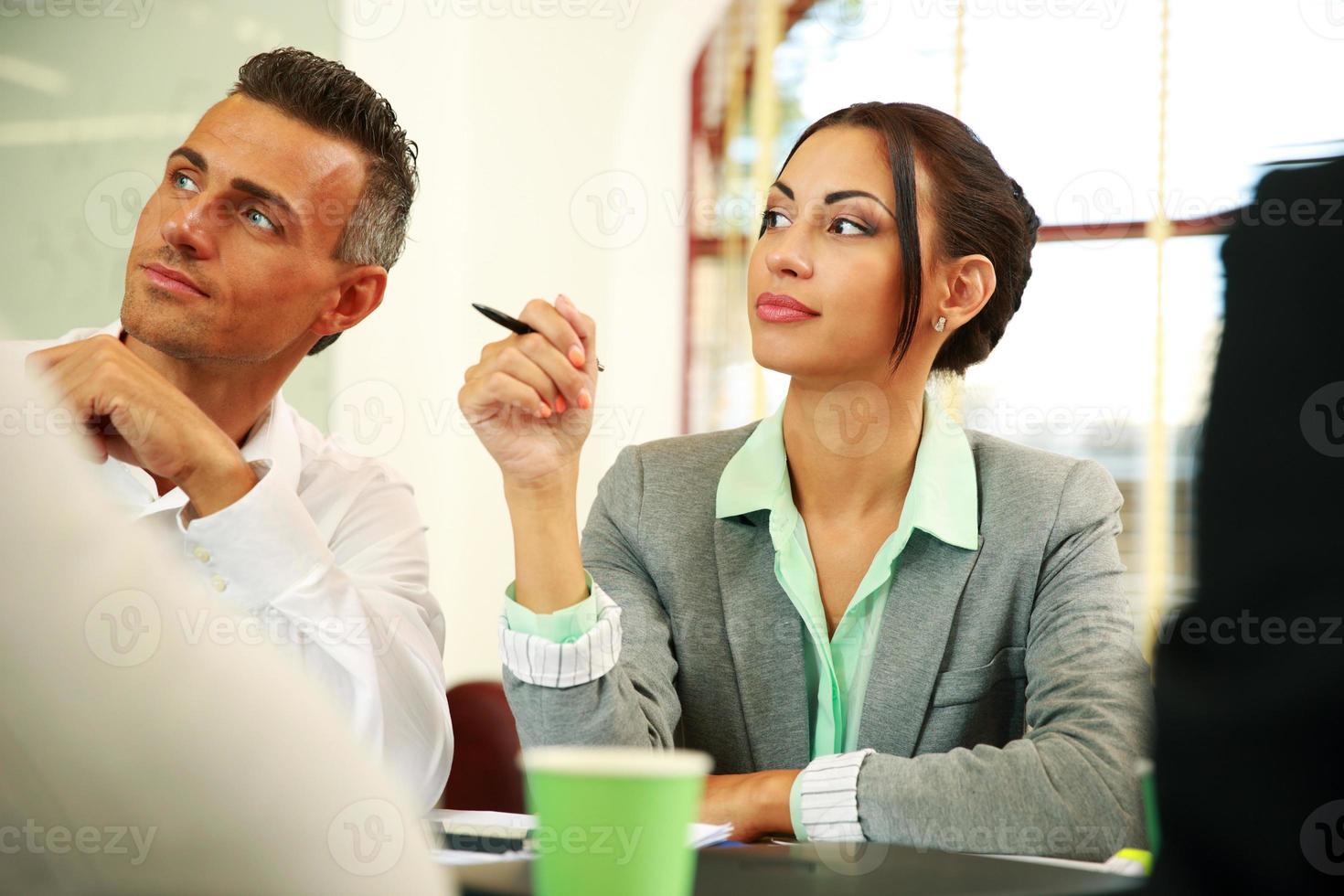 mensen uit het bedrijfsleven zitten rond een tafel foto