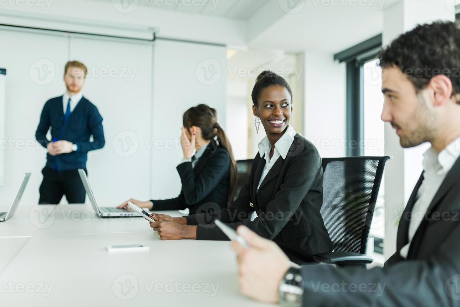 jonge mensen uit het bedrijfsleven zitten aan een conferentietafel foto